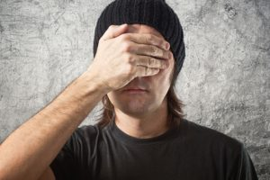 Portrait of Casual Man with Black Cap covering face in disbelief against grunge background